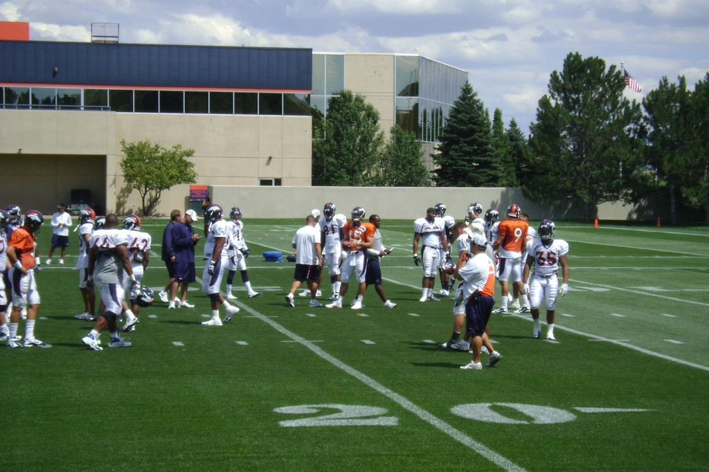 Tim Tebow (wearing orange #15 jersey) and fellow teammates gather to start training camp in 2010, his rookie season.
