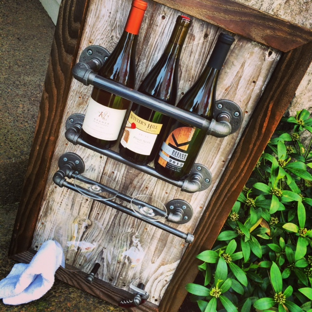 This rack displays bottles in the upright position. It has stemware holders like the other one, but also knobs for hanging barware: towels, corkscrews, etc... | Julia Crowley