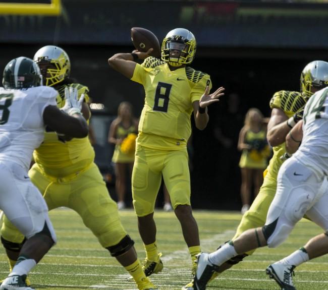 Oregon Quarterback Marcus Mariota passes against Michigan State. Photo-Dave  Peaks