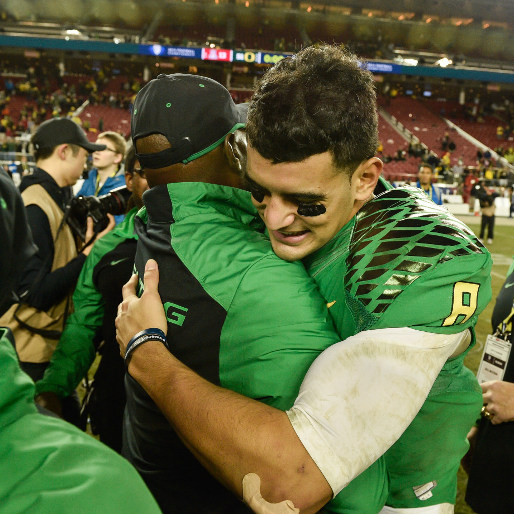 Marcus Mariota embraces defensive coordinator Don Pellum after the 51-13 win against the Arizona Wildcats on Dec. 5, 2014. | Eugene Johnson/EDN